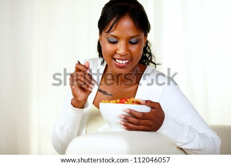 Portrait of a young black woman having healthy breakfast while is sitting on couch at home indoor - stock photo