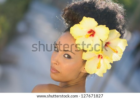 Portrait of a young black woman, model of fashion, with big flowers in her hair - stock photo