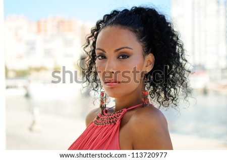 Portrait of a young black woman, model of fashion, with pink dress and earrings, with afro hairstyle - stock photo