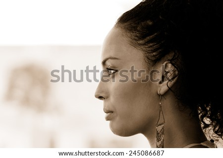 Portrait of a young black woman profile, model of fashion, with pink dress and earrings. Afro hairstyle  - stock photo