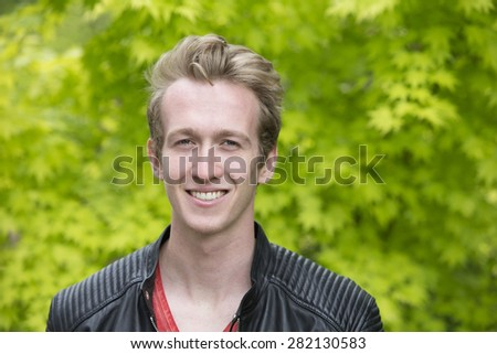 portrait of a young blond man in a black leather jacket - stock photo