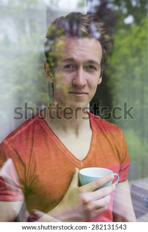 portrait of a young blond man looking out of a window with a cup in his hands - stock photo