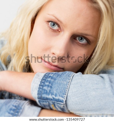 Portrait of a young blond woman with jeans jacket looking with a soft smile and lying on her arms, studio fashion shot with a selective focus at the eyes - stock photo