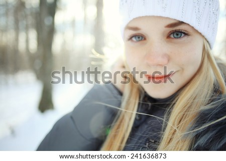 portrait of a young blonde girl in winter forest in the park - stock photo