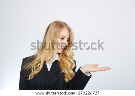 Portrait of a young blonde woman in a suit, with her hand outstretched, as though she is presenting something - stock photo