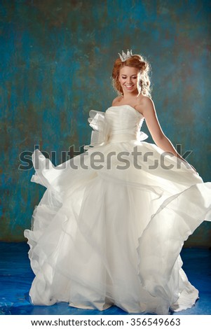 Portrait of a young blonde woman with chic thick hair, dancing and laughing in a white dress and a crown on her head, like a princess, a full-length - stock photo