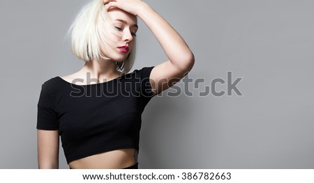 Portrait of a young blonde woman with closed eyes and red lipstick on her lips in a short black T-shirt - stock photo