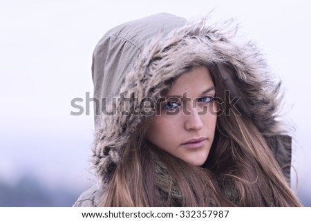 Portrait of a young blue eyed woman with a hood on his head - stock photo