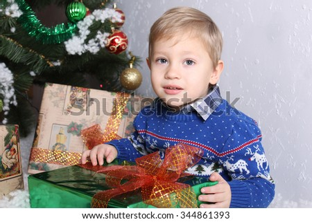 Portrait of a young boy behind the child a Christmas tree. The boy is holding a New Year green gift with orange bow. A child in winter blue sweater. On sweater ornament deer white. Blond.  - stock photo
