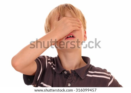 Portrait of a young boy covering his eyes on white background - stock photo