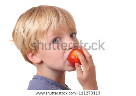 Portrait of a young boy eating a tomato - stock photo