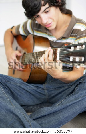 Portrait of a young boy playing guitar - stock photo