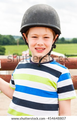 Portrait of a young boy wearing a horse riding hat - stock photo