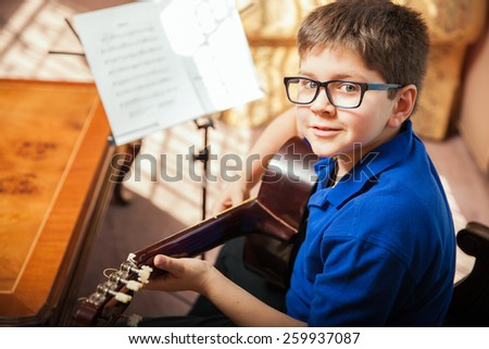 Portrait of a young boy with glasses practicing a song during a guitar lesson at home - stock photo