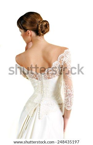 portrait of a Young bride wearing a White lace wedding gown photographed from the back isolated on White background - stock photo