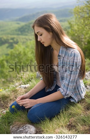 Portrait of a young brunette beauty observing the view. - stock photo