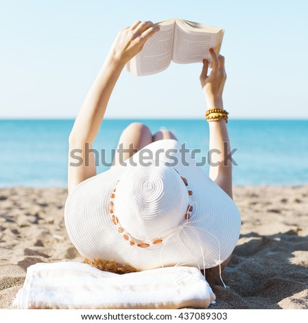 Portrait of a young brunette relaxing on the beach, reading a book - stock photo