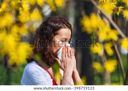 Portrait of a young brunette woman blowing her nose when standing close to flowers in a park - stock photo