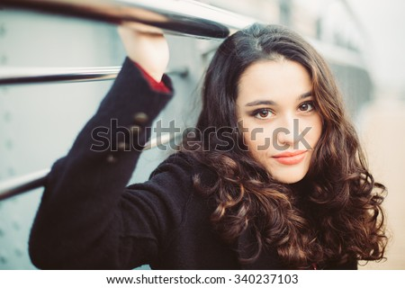 Portrait of a young brunette woman clutching a handrail outdoors with sweet smile - stock photo