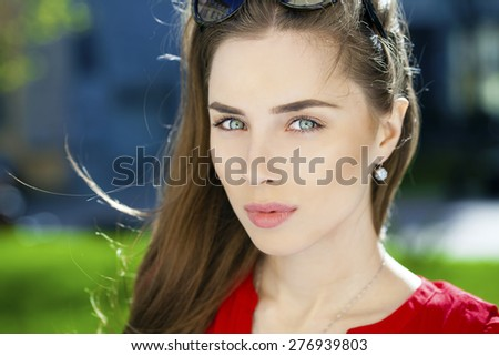 Portrait of a young brunette woman on summer street  - stock photo