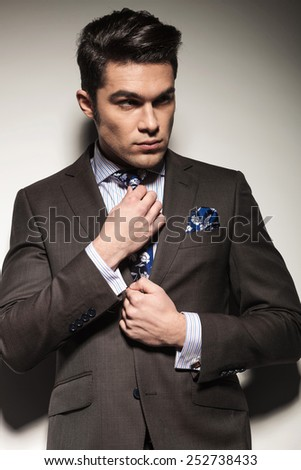 Portrait of a young business man fixing his tie while looking away from the camera. On grey studio background. - stock photo