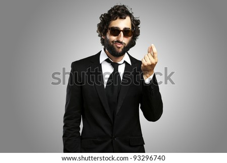 portrait of a young business man gesturing money over a grey background - stock photo