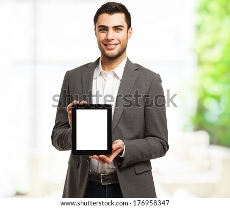 Portrait of a young business man holding his tablet - stock photo