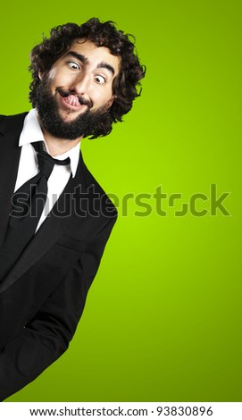 portrait of a young business man showing his tongue over a green background - stock photo
