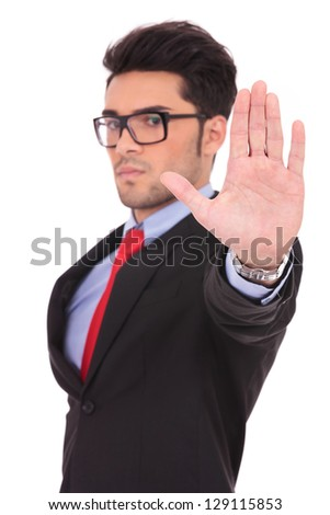 portrait of a young business man showing the stop sign with his palm and looking at the camera, on white - stock photo