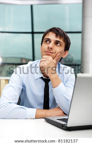 Portrait of a young business man sitting by his laptop in the office - stock photo