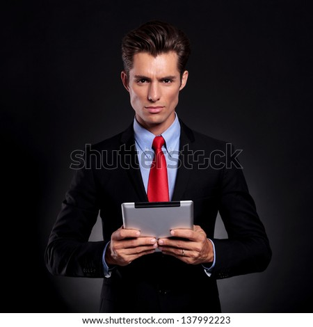 portrait of a young business man standing against a black background and holding a tablet with both his hands while looking at the camera with a serious expression - stock photo