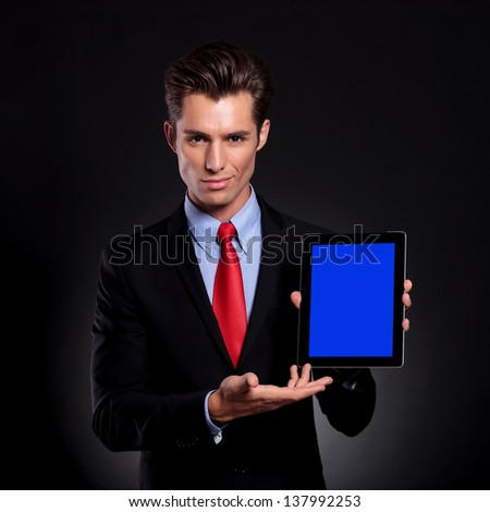 portrait of a young business man standing against a black background presenting a tablet with a faint smile on his face - stock photo