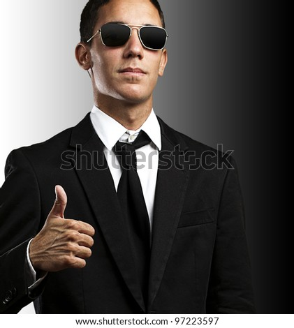 portrait of a young business man with sunglasses with thumb up against a black background - stock photo
