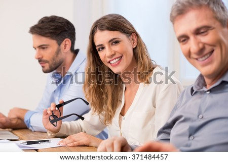 Portrait of a young business woman looking at camera during a meeting. Businesspeople in a meeting. Portrait of businesswoman during a business conference in a boardroom looking at camera and smiling. - stock photo