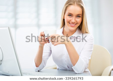 Portrait of a young business woman using computer at office - stock photo