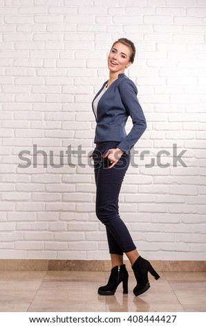 Portrait of a young business woman using laptop at office smiling - stock photo
