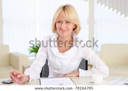 portrait of a young business woman with papers in the offcie - stock photo