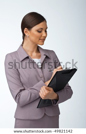 Portrait of a young business woman writing something on the folder with papers - stock photo