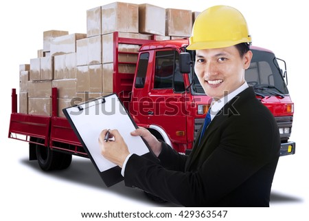 Portrait of a young businessman holding a clipboard with a logistic truck on the background - stock photo