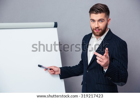 Portrait of a young businessman in suit presenting something on blank board over gray background - stock photo