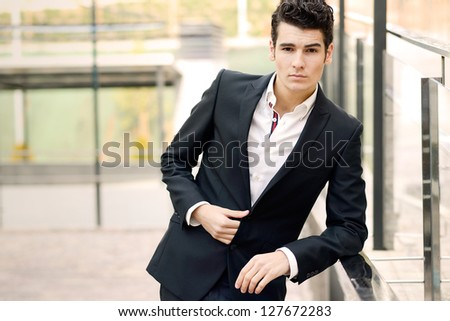 Portrait of a young businessman in urban background - stock photo