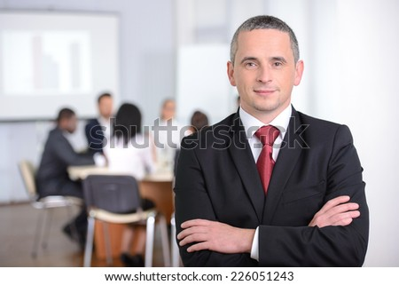 Portrait of a young businessman, people group in background at modern bright office indoors - stock photo