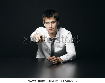 Portrait of a young businessman pointing at you - stock photo