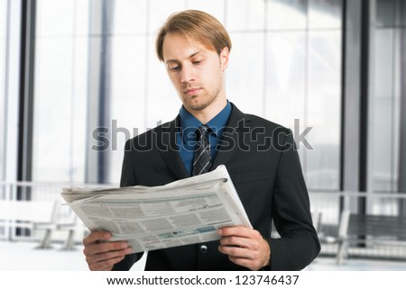 Portrait of a young businessman reading a newspaper - stock photo