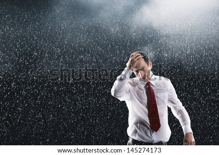 Portrait of a young businessman running fingers through wet hair in the rain - stock photo