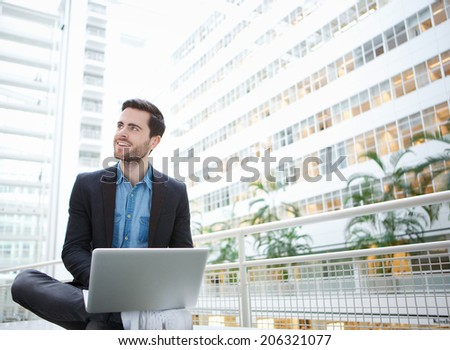 Portrait of a young businessman smiling with laptop inside building - stock photo