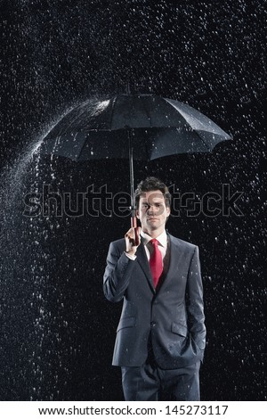Portrait of a young businessman standing under umbrella in rain against black background - stock photo