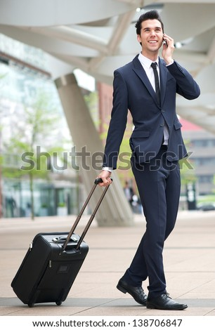 Portrait of a young businessman traveling with phone and bag - stock photo