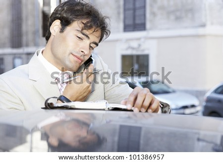 Portrait of a young businessman using a cell phone and taking notes, leaning on a car in the city. - stock photo