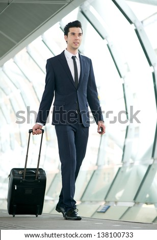Portrait of a young businessman walking in subway station with bag - stock photo